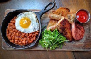 Tart's L.A. Fry-up is bologna, pork belly and chicken apple sausage on toast with baked beans and a sunny-side up egg.