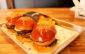A trio of mini burgers (lamb with sautéed mushrooms, beef with sunny-side-up egg and salmon with pineapple) at Burgerim Montclair. (Evan Solano/LOL-LA)